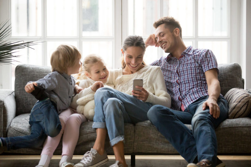 Cheerful young family with kids laughing watching funny video on smartphone sitting on couch together, parents with children enjoying playing games or entertaining using mobile apps on phone at home